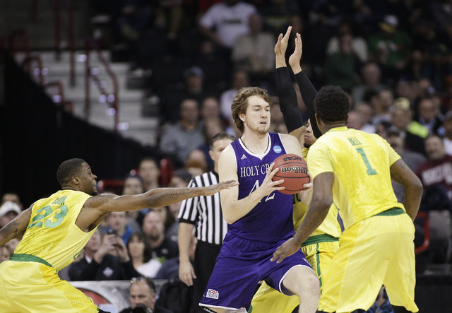 Holy Cross center Matt Husek, center, tries to drive around Oregon forwards Jordan Bell (1), Elgin Cook (23) and Dillon Brooks during the second half of a first-round men's college basketball game ...