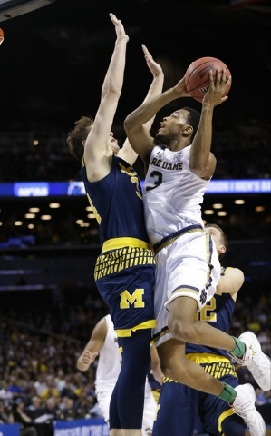 Notre Dame's V.J. Beachem (3) shoots over Michigan's Mark Donnal (34) during the second half of a first-round men's college basketball game in the NCAA Tournament, Friday, March 18, 2016, in New Y ...