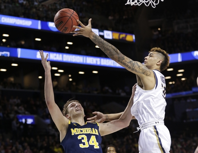 Notre Dame's Zach Auguste (30) and Michigan's Mark Donnal (34) fight for the ball during the first half of a first-round men's college basketball game in the NCAA Tournament, Friday, March 18, 201 ...