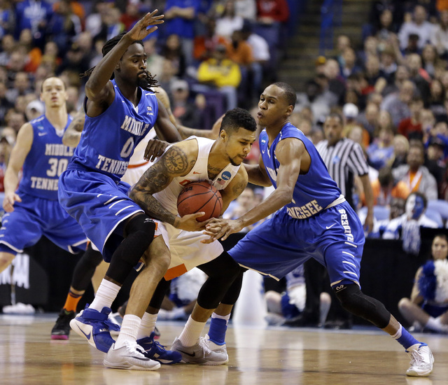 Syracuse's Michael Gbinije, center, holds the ball as Middle Tennessee's Darnell Harris, left, and Jaqawn Raymond defend during the first half in a second-round men's college basketball game in th ...
