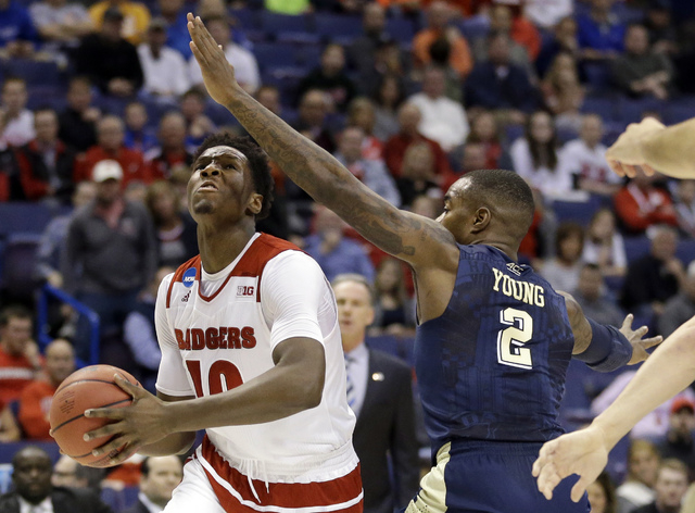 Wisconsin's Nigel Hayes, left, heads to the basket as Pittsburgh's Michael Young defends during the first half in a first-round men's college basketball game in the NCAA tournament, Friday, March  ...
