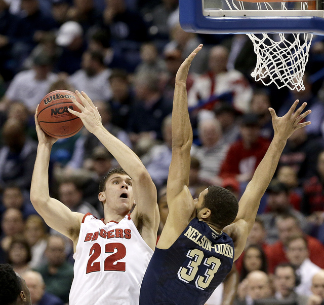 Wisconsin's Ethan Happ (22) shoots under pressure from Pittsburgh's Alonzo Nelson-Ododa (33) during the second half of a first-round men's college basketball game in the NCAA Tournament, Friday, M ...