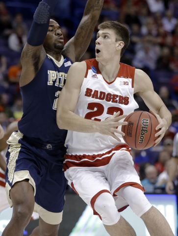 Wisconsin's Ethan Happ, right, looks to the basket as Pittsburgh's Michael Young defends during the first half in a first-round men's college basketball game in the NCAA tournament, Friday, March  ...