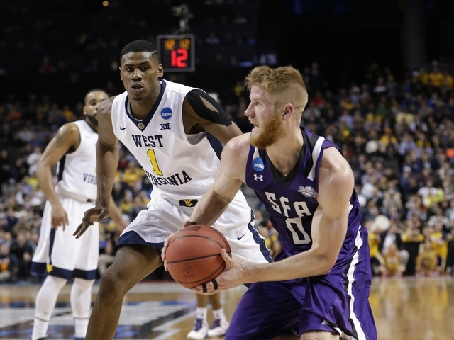 Stephen F. Austin's Thomas Walkup (0) drives past West Virginia's Jonathan Holton (1) during the second half of a first-round men's college basketball game in the NCAA Tournament,Friday, March 18, ...