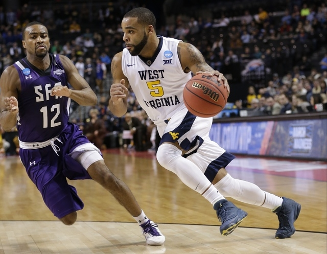 West Virginia's Jaysean Paige (5) drives past Stephen F. Austin's Dallas Cameron (12) during the first half of a first-round men's college basketball game in the NCAA Tournament,Friday, March 18,  ...