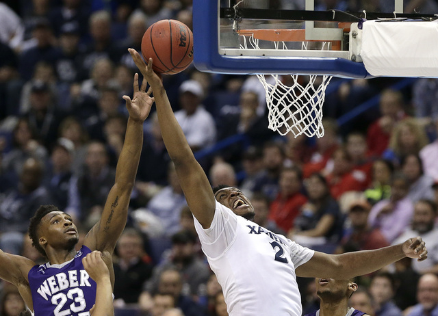 Xavier's James Farr (2) gets past Weber State's Richaud Gittens (23) to put up a shot during the first half of a first-round men's college basketball game in the NCAA Tournament, Friday, March 18, ...
