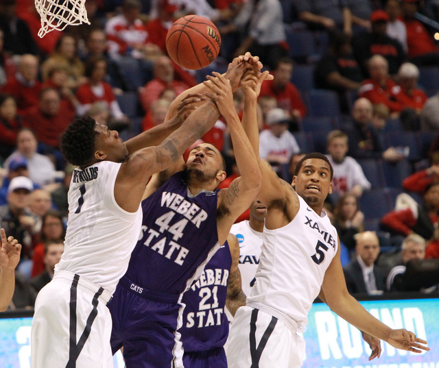 Weber State's Zach Braxton (44) competes for a rebound against Xavier forward Jalen Reynolds, left, and guard Trevon Bluiett during the first half of an NCAA college basketball game in the NCAA me ...