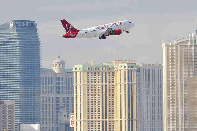 A Virgin America aircraft passes by the Strip after taking off from McCarran International airport in Las Vegas on Monday, Jan. 12, 2015. (David Becker/Las Vegas Review-Journal)