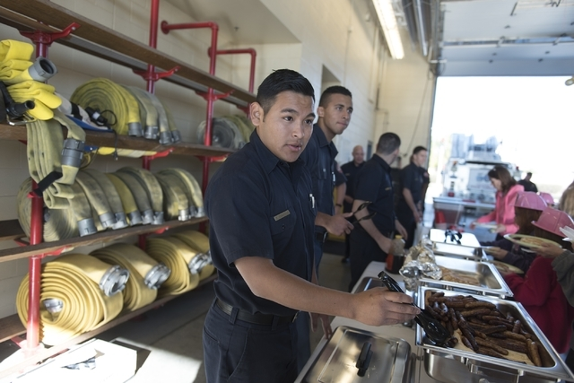 Francisco Corrilo, left, and Oscar Pavon, members of the North Las Vegas Explorer Program, serve food during a pancake breakfast event at North Las Vegas Fire Department's Fire Station 56 at 3475  ...