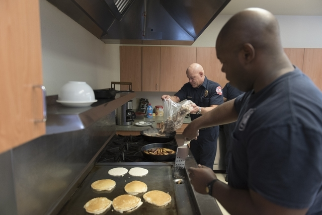 Engineer Joel Collins, left, and firefighter/paramedic Omari Stephens prepare food during a pancake breakfast event at North Las Vegas Fire Department's Fire Station 56 at 3475 Elkhorn Road, Satur ...