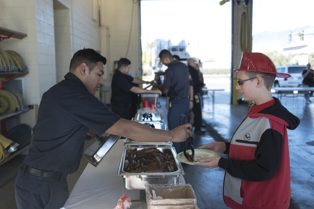 Francisco Corrilo, a member of the North Las Vegas Explorer Program, left, serves sausage to 11-year-old Koen Flyn during a pancake breakfast event at North Las Vegas Fire Department's Fire Statio ...