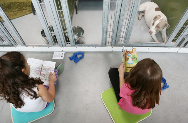 Sewell first-graders Geraldine Bosch, left, and Kenzli Page read to dogs including a pit bull terrier named Honey, top right, at The Animal Foundation March 1. Ronda Churchill/View
