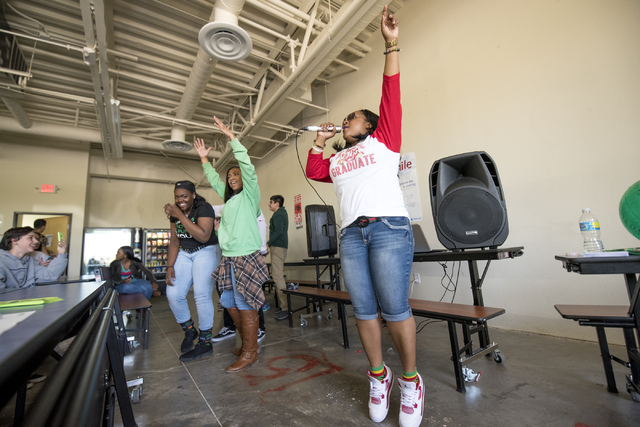 Elizabeth Elie, right, who goes by the name Lizzie G, performs rap songs that promote positive messages as students dance with her at Quest Preparatory Academy, 7485 W. Azure Drive, March 17. Josh ...