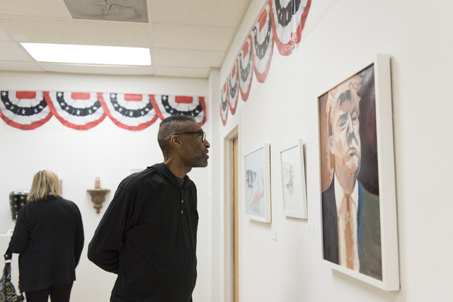 "Kenn Ruffin views the ""MUG SHOTS #3"" group show at Left of Center Art Gallery March 12. Jason Ogulnik/View"