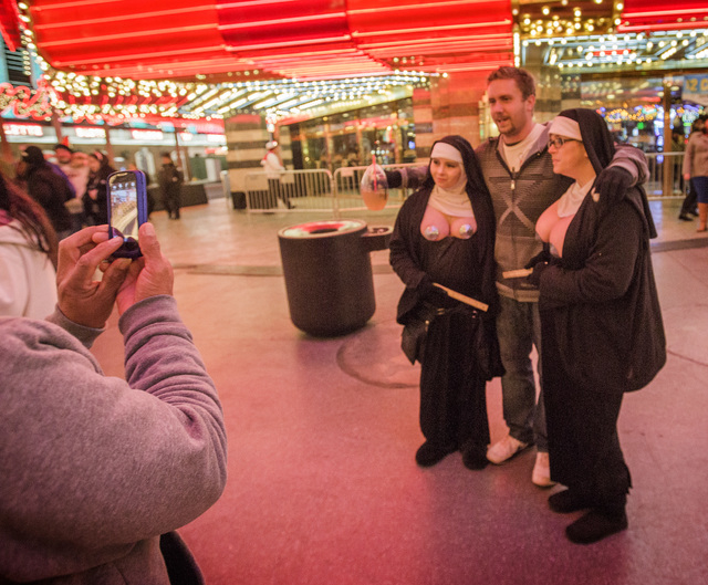 A man poises with buskers at Fremont Street Experience. (Jeff Scheid/Las Vegas Review-Journal)