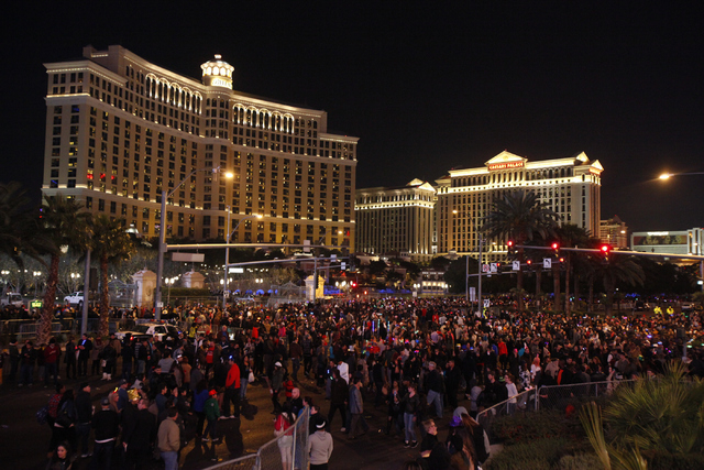 New Years Eve revelers walk around outside the Bellagio, on left, on the Las Vegas Strip on Tuesday, Dec. 31, 2013. (Chase Stevens/Las Vegas Review-Journal)