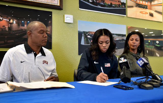 Bishop Gorman high jumper Vashti Cunningham, between her father, Randall Cunningham, left, and mother Felicity Cunningham signs a document at a news conference at Remnant Ministries Monday, March  ...