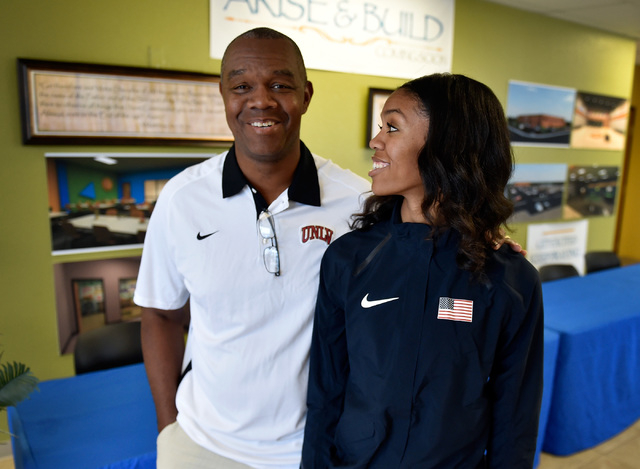 Bishop Gorman high jumper Vashti Cunningham, right, looks up to her father, former UNLV and NFL quarterback Randall Cunningham, after a news conference at Remnant Ministries Monday, March 21, 2016 ...