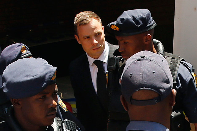 South African Olympic and Paralympic sprinter Oscar Pistorius, center, is escorted to a police van after his sentencing at the North Gauteng High Court in Pretoria, Oct. 21, 2014. Pistorius was se ...