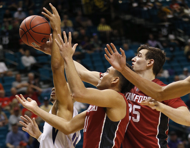 Washington guard Andrew Andrews, from left, Stanford guard Dorian Pickens and Stanford forward Rosco Allen battle for a rebound during the second half of an NCAA college basketball game in the fir ...
