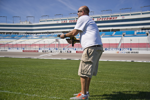 Dale Pantelakis, of Sport Designs International, measures and marks out the main logo for the Kobalt Tools 400 on the grass in front of the grandstands at Las Vegas Motor Speedway on Wed, Feb. 24, ...