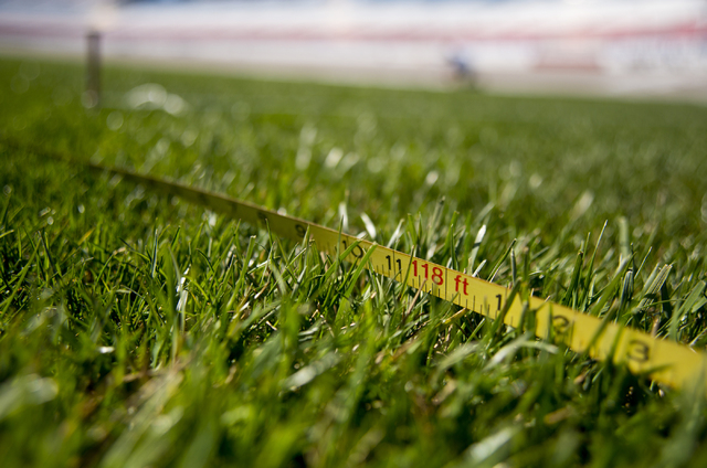 A tape measure used by Dale Pantelakis, of Sport Designs International, to measure out the main logo for the Kobalt Tools 400 lies on the grass in front of the grandstands at Las Vegas Motor Speed ...