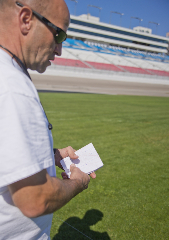 Dale Pantelakis, of Sport Designs International, quickly references his hand drawn measurements for the massive main logo of the Kobalt Tools 400 at Las Vegas Motor Speedway on Wed, Feb. 24, 2016. ...