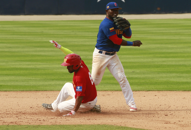 Spain's Oscar Angulo, left, is tagged out by Colombia's second baseman Dilson Herrera during the World Baseball Classic qualifying match in Panama City, Thursday, March 17, 2016. Colombia won 9-2. ...