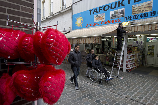 People pass a shop in the Molenbeek neighborhood of Brussels, Belgium, Saturday, March 19, 2016, where fugitive Salah Abdeslam was arrested after a four-month manhunt. (AP Photo/Peter Dejong)