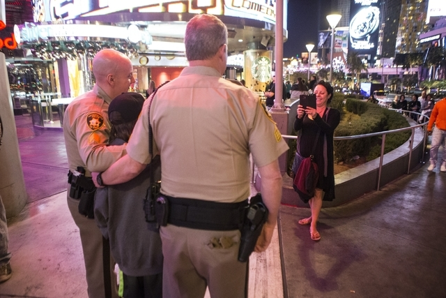 Las Vegas police Sgt. Bill Steinmetz, left, and Sgt. William Jones take a photo with passerby on the Strip near Planet Hollywood casino-hotel during their afternoon shift on Friday, Feb. 12, 2016, ...