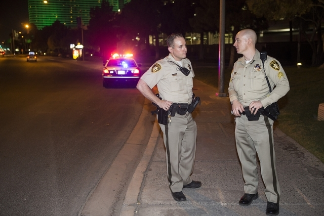 Las Vegas police Sgt. Bill Steinmetz, right, checks on officer Chris Colacurci after he gave chase to a man with a felony warrant near E. Tropicana Avenue and Koval Lane on Friday, Feb. 12, 2016,  ...