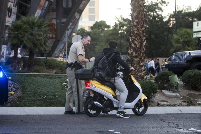 A Las Vegas police officer speaks with a scooter driver on the Strip near E. Flamingo Road on Friday, Feb. 12, 2016, in Las Vegas. Erik Verduzco/Las Vegas Review-Journal Follow @Erik_Verduzco