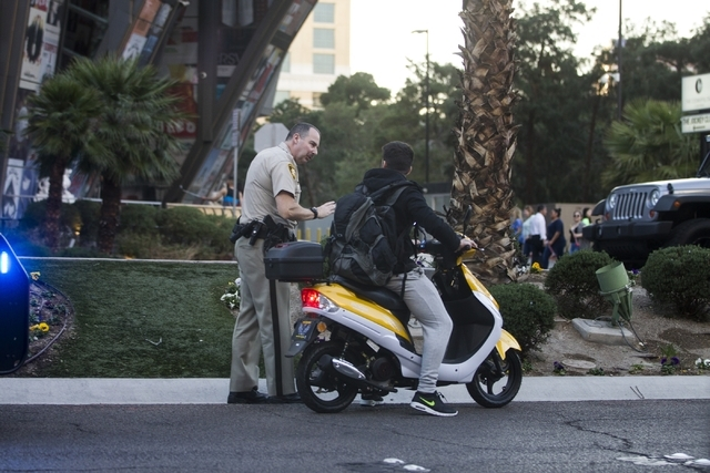 A Las Vegas police officer speaks with a scooter driver on the Strip near E. Flamingo Road on Friday, Feb. 12, 2016, in Las Vegas. Erik Verduzco/Las Vegas Review-Journal Follow @Erik_Verduzco