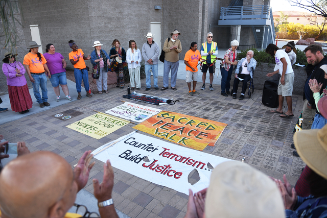 Peace walkers gather around a circle for group prayer just before their 60-mile pilgrimage starting from the National Atomic Testing Museum in Las Vegas to the Nevada Test Site during the annual S ...