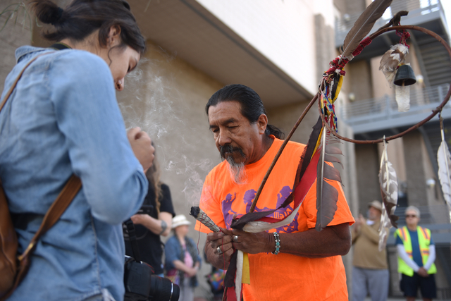 Willie Fragosa, right, blesses Tami Yuron and other peace walkers using sage and a prayer stick before they begin their 60-mile pilgrimage starting from the National Atomic Testing Museum in Las V ...
