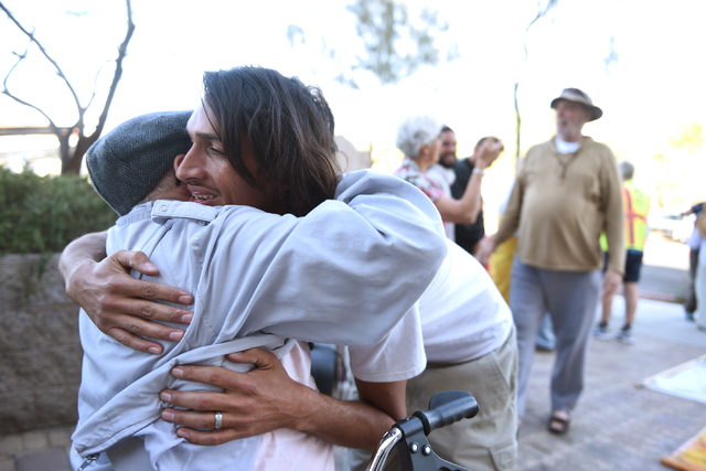 Nevada Desert Experience co-organizer Robert Majors, left, hugs Jerry Zawada just before he and other peace walkers begin their 60-mile pilgrimage starting from the National Atomic Testing Museum  ...