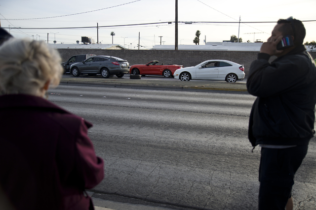 People stand on the sidewalk near the scene of an accident involving at least six vehicles just north of the Washington Avenue and Rancho Drive intersection in Las Vegas on Tuesday, March 8, 2016. ...