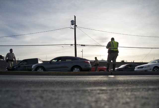 Police officers measure and photograph the scene of an accident involving at least six vehicles just north of the Washington Avenue and Rancho Drive intersection in Las Vegas on Tuesday, March 8,  ...