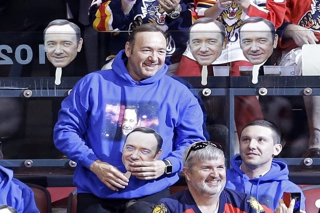 Actor Kevin Spacey smiles as he acknowledges the fans as he hold a mask during an NHL hockey game between the Florida Panthers and the Detroit Red Wings in Sunrise, Fla., Saturday, March 19, 2016. ...