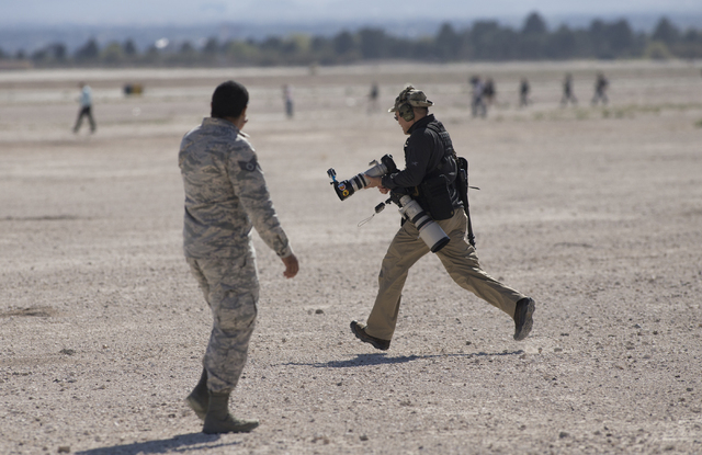 Photographers scramble to get to an adjacent runway to catch a departing aircraft during the Red Flag air combat exercise at Nellis Air Force Base on Tuesday, March 8, 2016, in Las Vegas.  Benjami ...