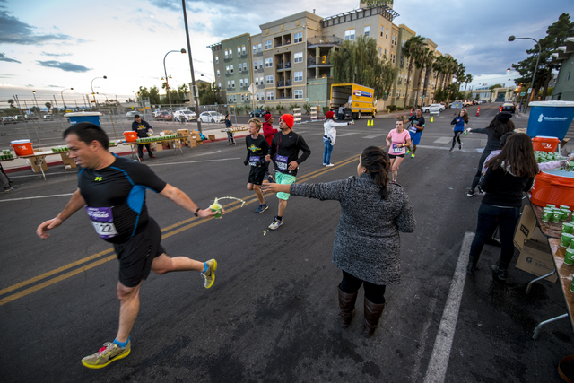Refreshments are passed to runners in downtown Las Vegas during the Rock-n-Roll Marathon on Sunday, Nov. 15, 2015. Joshua Dahl/Las Vegas Review-Journal