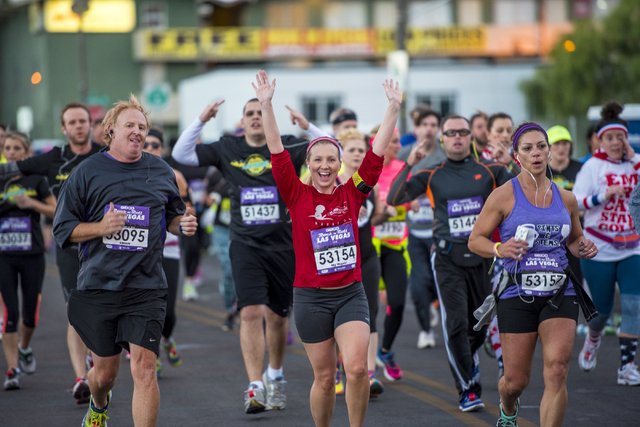 A runner puts her arms up in downtown Las Vegas during the Rock-n-Roll Marathon on Sunday, Nov. 15, 2015. Joshua Dahl/Las Vegas Review-Journal