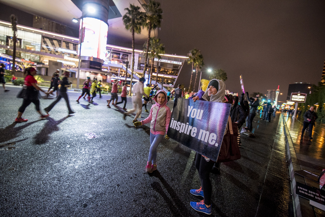 A sign is held up as runners pass by on Las Vegas Blvd during the Rock-n-Roll Marathon in Las Vegas on Sunday, Nov. 15, 2015. Joshua Dahl/Las Vegas Review-Journal
