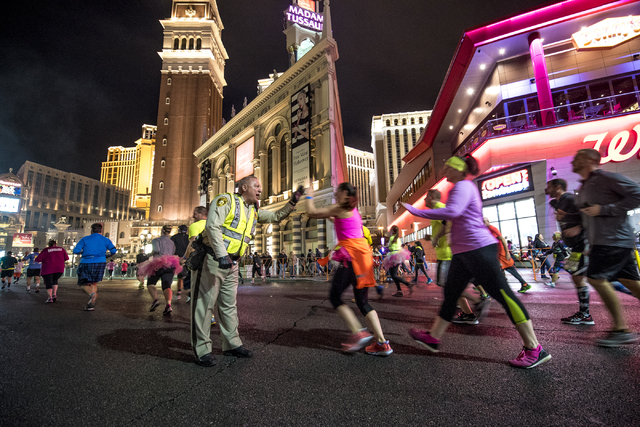A police officer high fives runners on Las Vegas Blvd during the Rock-n-Roll Marathon in Las Vegas on Sunday, Nov. 15, 2015. Joshua Dahl/Las Vegas Review-Journal