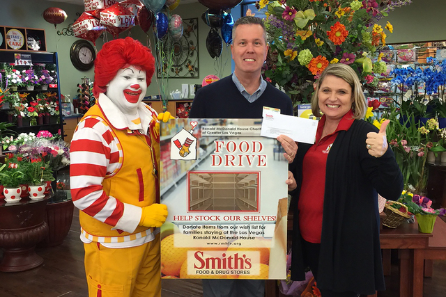 Ronald McDonald, Bob Day, human resources coordinator of Smith's Food and Drug, and Alyson McCarthy, executive director of Ronald McDonald House Charities, smile during the annual food drive for ...