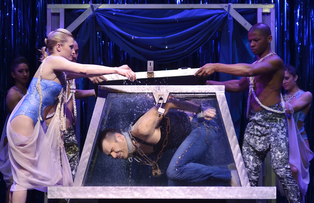 "Cast members Sarah Vose, left, and Malachi Durant, right, prepare to put the lid on and lock a water-filled box as a chained Jan Rouven tries to escape during ""The New Illusions"" at the Tropicana  ..."