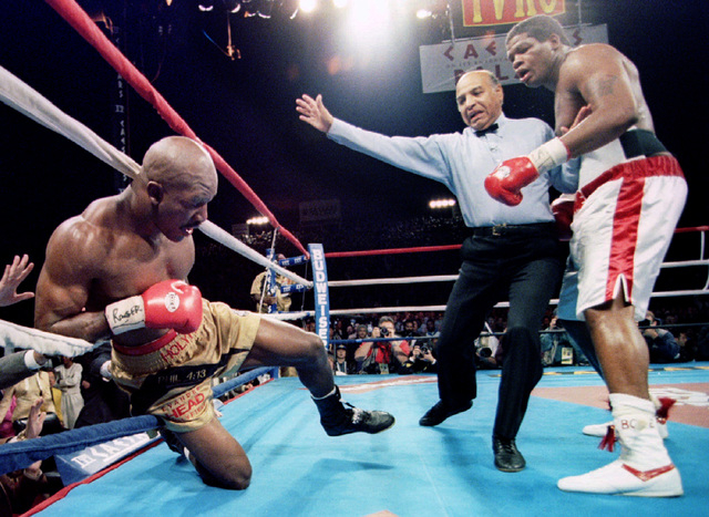 Evander Holyfield (L) falls into the ropes after a knockdown punch by Riddick Bowe in the eighth round of their heavyweight bout at Caesars Palace in Las Vegas, November 4. Referee Joe Cortez stop ...