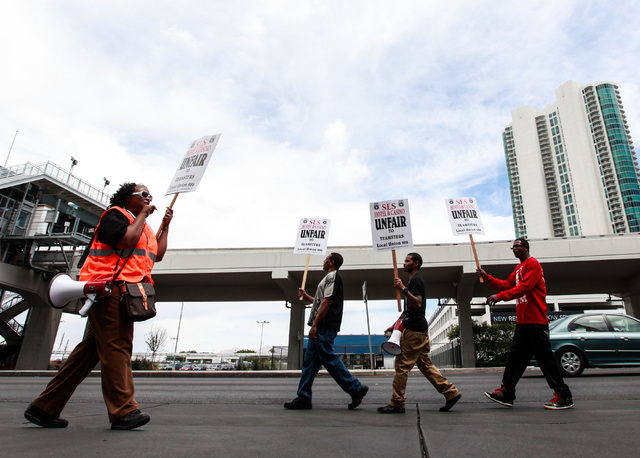Tamura Jamison, left, speaks over a megaphone as people with Teamsters Local 986 protest outside of the SLS hotel-casino by the Paradise Road entrance  in Las Vegas on Wednesday, May 20, 2015. (Ch ...