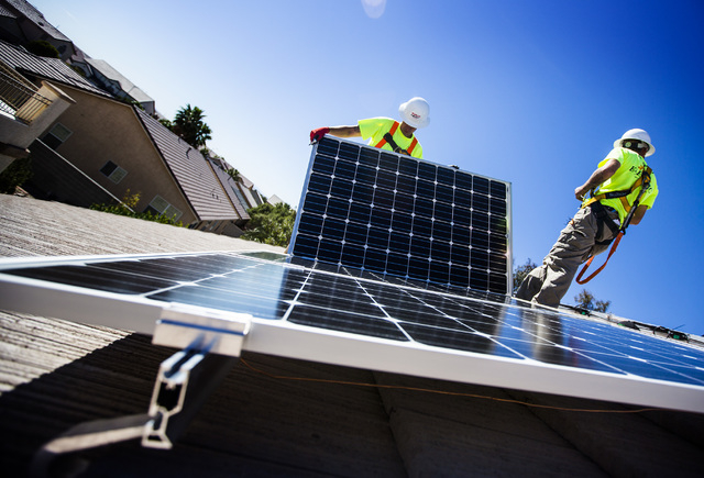Matt Neifeld, left, and Jacy Sparkman with Robco Electric installs solar panels at a home in northwest Las Vegas on Friday March 13, 2015. (Jeff Scheid/Las Vegas Review-Journal)
