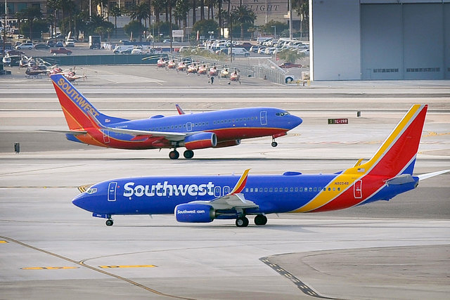 Two Southwest Airlines jets pass each other as one departs and the other taxis at McCarran International airport in Las Vegas on Jan. 12, 2015. (David Becker/Las Vegas Review-Journal)